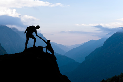 Teamwork couple helping hand trust assistance silhouette in mountains, sunset. Team of climbers man and woman hiker, help each other on top of mountain, climbing assistance, beautiful sunset landscape in Himalayas Nepal